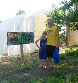 Jacob Marintzer and his son outside of the giant pumpkin greenhouse